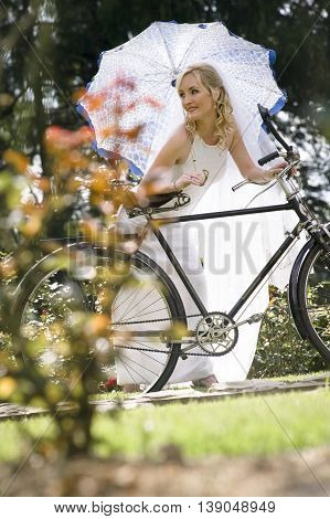 Bride Leaning On A Bycicle With A Parasol Or Umbrella