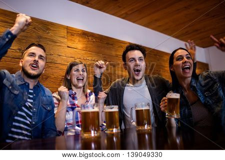 Friends enjoying with beer mugs at table in restaurant