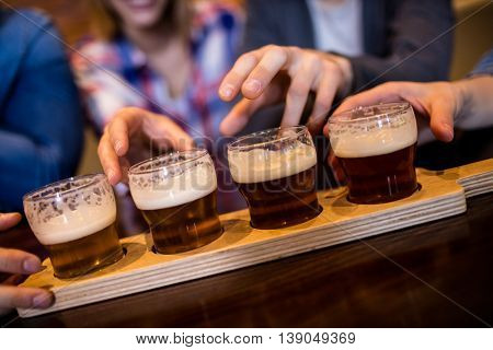 Cropped image of friends taking beer glasses at restaurant