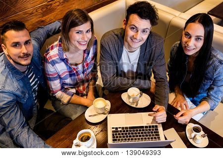 High angle portrait of friends using laptop at restaurant