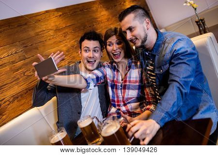 Friends enjoying while taking selfie through mobile phone at restaurant