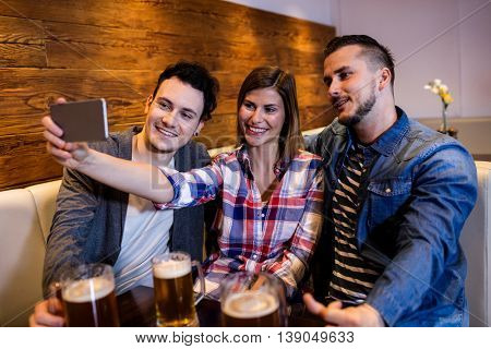 Happy friends taking selfie through mobile phone at restaurant