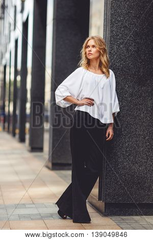 Young pensive business lady in white blouse and black pants leaned on the wall of modern building. Split toned photo