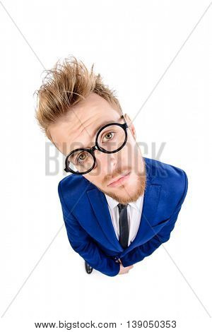 Funny smart guy in a suit and spectacles sad looking at the camera. Isolated over white.