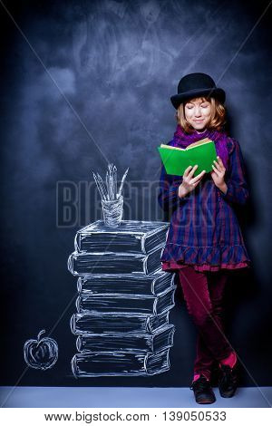 Educational concept. Teen girl reading a book on the background of the school board with drawn stack of books.