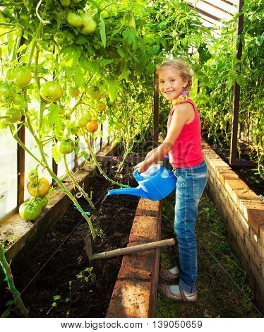 Child watering the garden. Girl helps to do the work in the greenhouse
