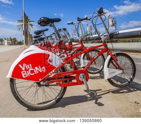 BARCELONA SPAIN - JULY 13 2016: Bicycles on a street of Barcelona. Public Service Vehicles bicycles Vodafone Bicing. Bicing is the name of a bicycle sharing system in Barcelona inaugurated on March 22 2007.