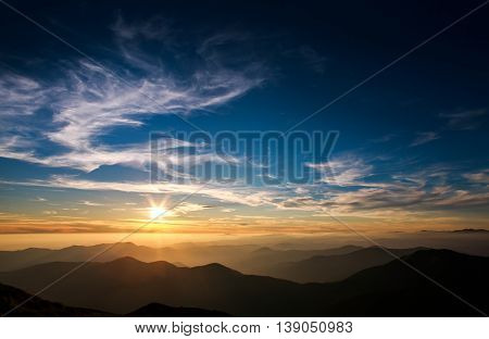 Magnificent sunset sky over silhouettes of the mountains