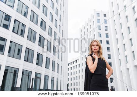 Business woman is nicely contrasted against white buildings dressed in black dress