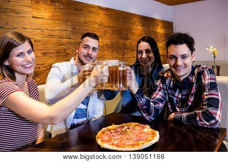 Portrait of young friends smiling while toasting beer at bar