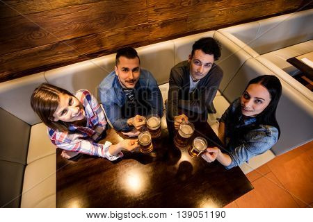 High angle view of friends enjoying beer at restaurant