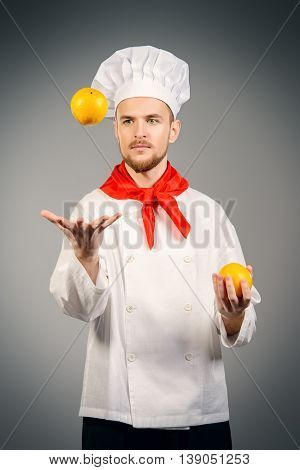 Professional male cook juggling with oranges. Healthy eating. Copy space. Studio shot.