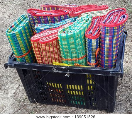 black plastic bin of rolled picnic mats in bright plaid colors, each mat tied with a red and orange strap, beach at Songkhla, Thailand