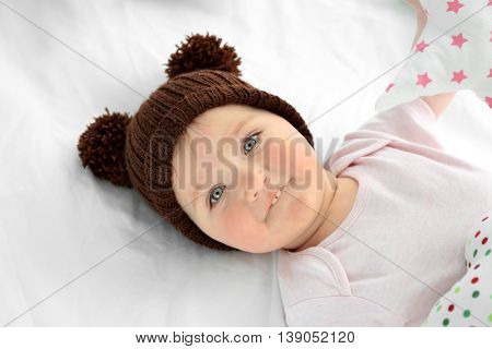 Adorable  baby girl in a hat on a white sheet