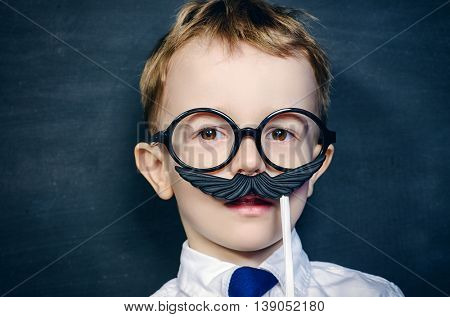 Funny little boy in round glasses plays with false mustache. Childhood concept. Emotions.