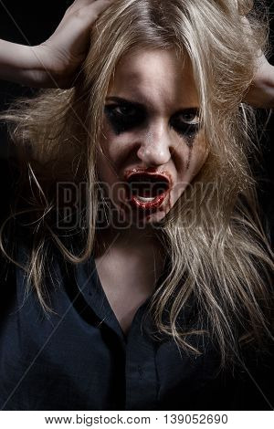 blond bloody witch screaming on black background