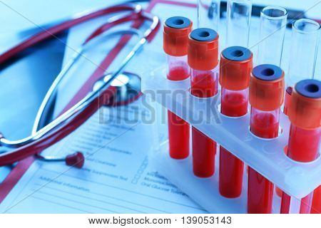 Blood samples and stethoscope on medical report
