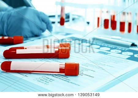 Blood samples and doctor hands on medical report