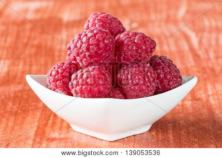 Fresh raspberries in white bowl on the wooden background