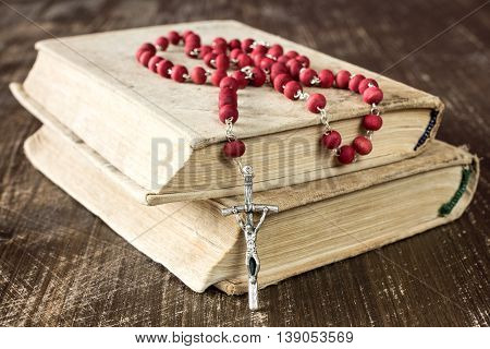 The rosary and old books on wooden background