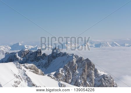sunny Dachstein Mountains extends over the clouds to the horizon