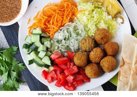 falafel plate on top to garnish carrot cabbage onion cucumbers tomatoes still life dish restaurant
