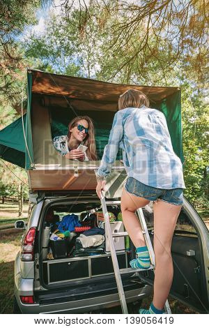 Young woman walking up ladder to tent over car while her female friend holding smartphone lying in tent