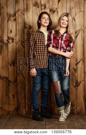 Two modern teenage boy and girl standing together by a wooden wall. Friendship. First love.