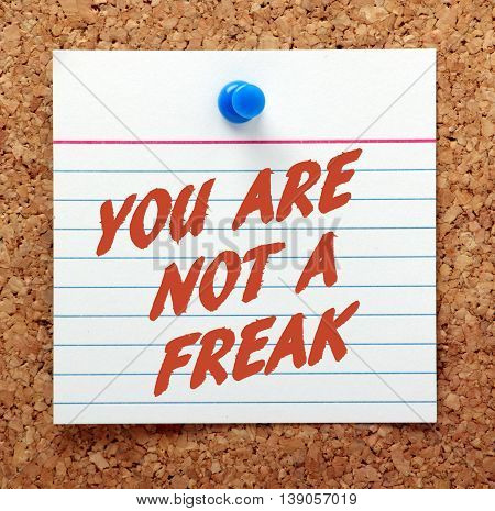 The words You Are Not A Freak in red text on a note card pinned to a cork notice board as a reminder that you are a person and deserve respect