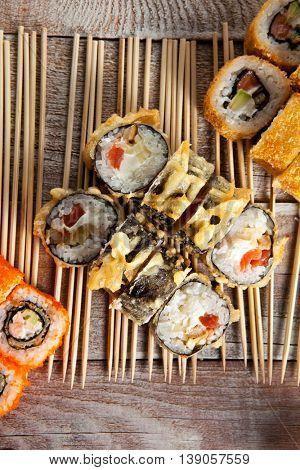 Set of Maki Sushi with Chopsticks Wooden Background