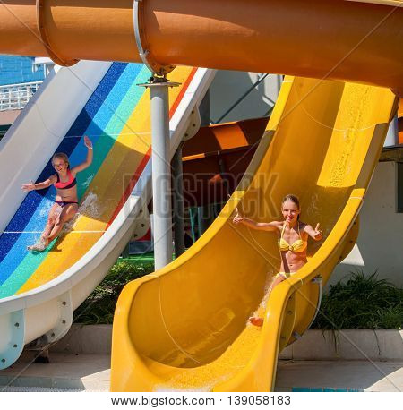 Two happy children on water slide at aquapark and thumb up. Summer holiday. There are two water slides in water park. Outdoor summer holiday.
