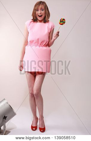 Studio shot of an attractive young woman isolated on grey mit lollipop in your hand