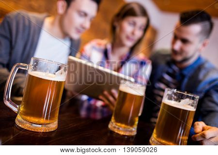 Beer mugs on table with friends at restaurant