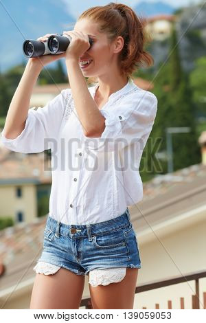 Summer holidays and tourism concept. Lovely tourist woman looking through binoculars .