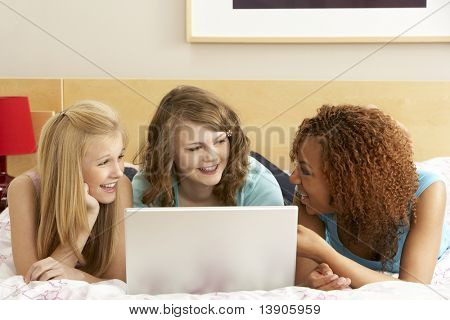 Group Of Three Teenage Girls Using Laptop In Bedroom