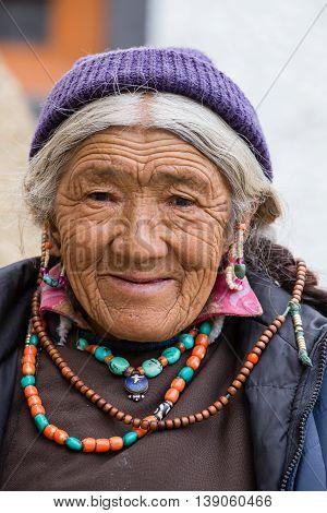 LAMAYURU INDIA - JUNE 13 2015: Unidentified buddhist old woman during mystical mask dancing Tsam mystery dance in time of Yuru Kabgyat Buddhist festival at Lamayuru Gompa Ladakh North India