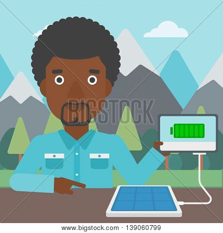 An african-american man charging tablet computer with solar panel on the background of mountains. Charging digital tablet from portable solar panel. Vector flat design illustration. Square layout.