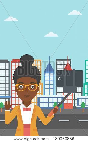 An african-american woman making selfie with a selfie-stick. An african-american woman taking photo with cellphone and waving on a city background. Vector flat design illustration. Vertical layout.