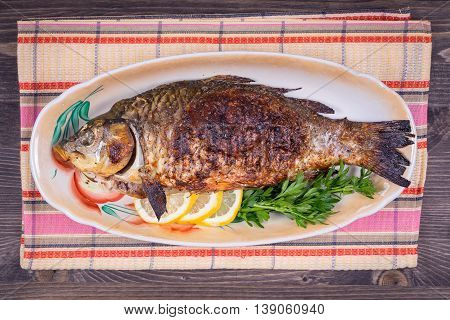 Fried fish carp on the plate close up