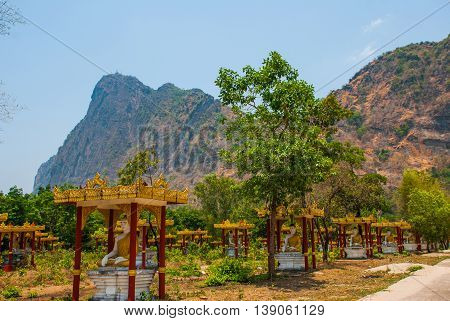 Many Statues Of The Buddhas Who Sit, Amid The Beautiful Landscape With Mountains In Sunny Day. Hpa-a