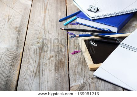 Still life, business, education concept. Assortment of office and school supplies and chalkboard on a rustic wooden table. Selective focus, copy space background