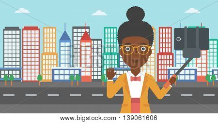 An african-american woman making selfie with a selfie-stick. An african-american woman taking photo with cellphone and waving on a city background. Vector flat design illustration. Horizontal layout.