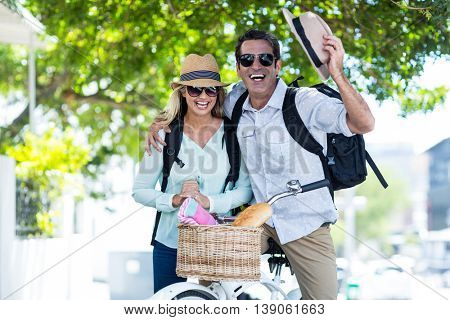 Cheerful mid adult couple with bicycle on street in city