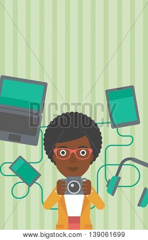 An african-american woman taking photo with digital camera. Woman surrounded with her electronic gadgets. Woman using many electronic gadgets. Vector flat design illustration. Vertical layout.