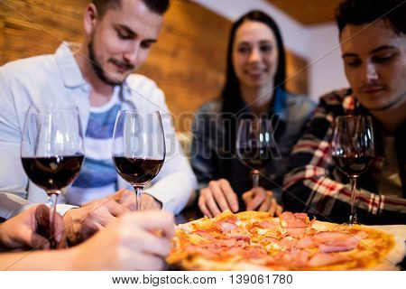 Friends enjoying pizza and wine at table in bar