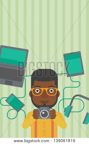 An african-american man taking photo with digital camera. Man surrounded with gadgets. Man using many electronic gadgets. Vector flat design illustration. Vertical layout.