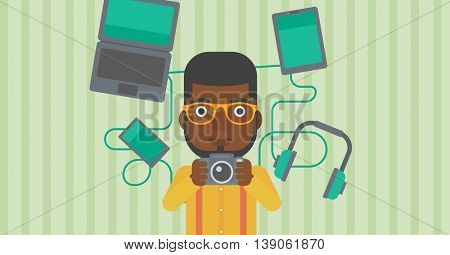 An african-american man taking photo with digital camera. Man surrounded with gadgets. Man using many electronic gadgets. Vector flat design illustration. Horizontal layout.