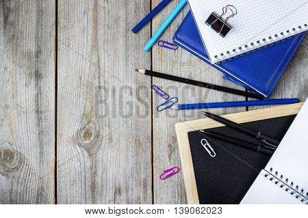 Still life, business, education concept. Assortment of office and school supplies and chalkboard on a rustic wooden table. Selective focus, copy space background, top view