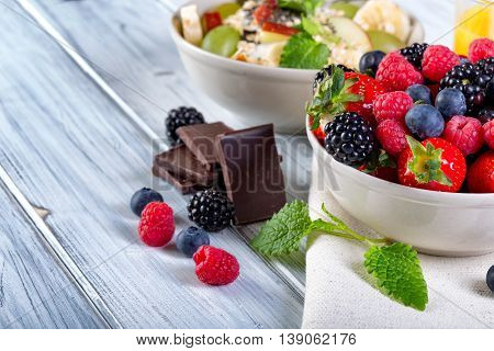 Bowl of fresh fruit. Blackberries; raspberries; blueberries on a bowl. Healthy breakfast. Vegetarian organic meal.