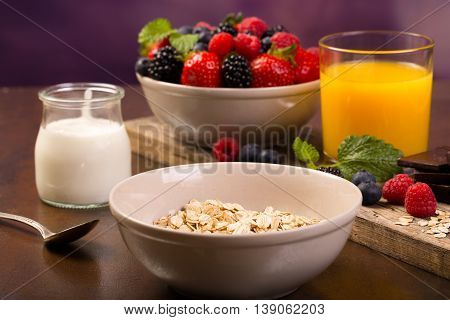 Spoon and yoghurt. Flavoring oatmeal with white yoghurt and some berries. Cup of fresh orange juice.